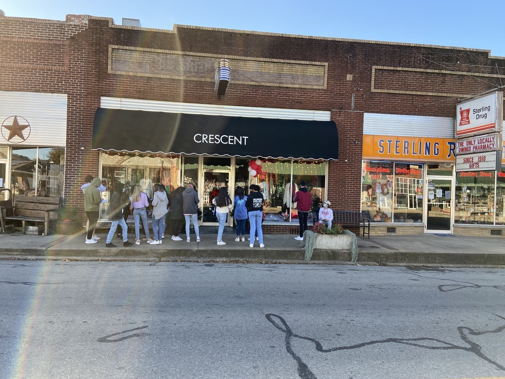 Students studying the front of Crescent Store