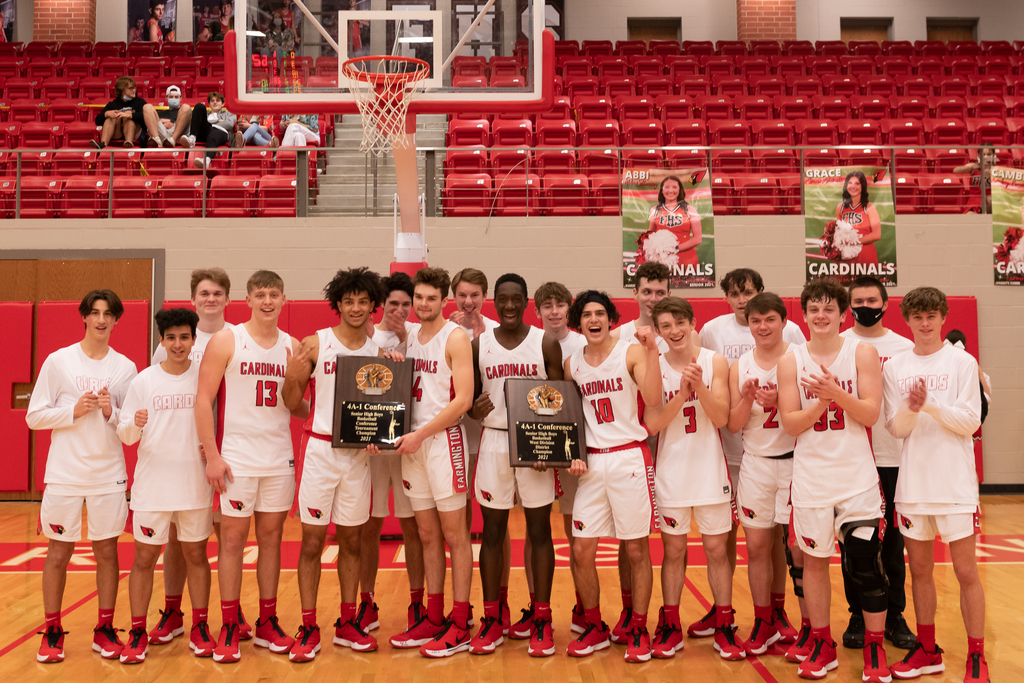 Farmington Varsity Boys Basketball team in uniform standing on the Cardinal Arena court holding their Championship trophies