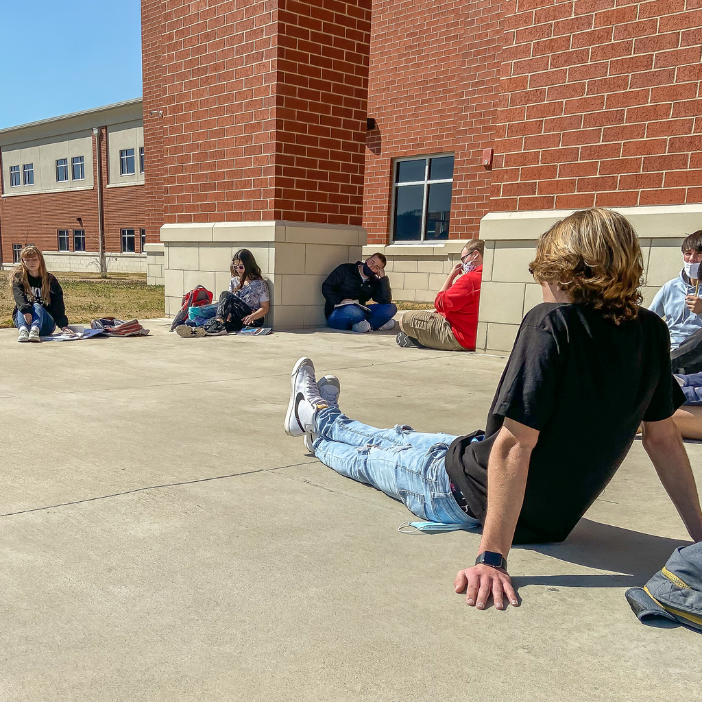 6 students sit outside the high school front doors in a social distanced circle discussing