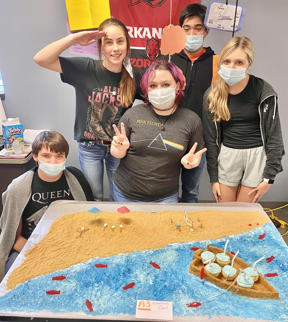 Students standing behind their sand and ocean cupcake creation